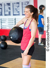 Woman Holding Medicine Ball In Fitness Club