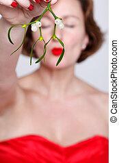 Woman holding mistletoe kissing