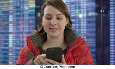 Woman holding mobile phone and looking at information board in airport