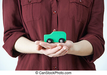 Woman Holding Model Car In Palm Of Hand