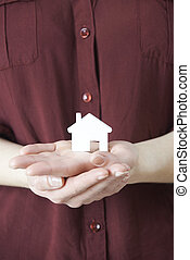 Woman Holding Model House In Palm Of Hand