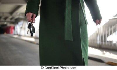 Woman holding modern car key walking to the car