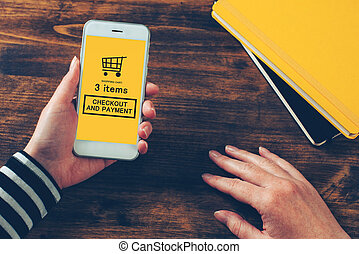 Woman holding modern mobile phone with online shopping application