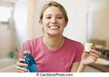 Woman Holding Mouthwash - A young woman shows off her teeth...