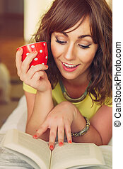 Woman Holding Mug and Reading Paperback Book