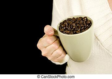 woman holding mug of coffee beans