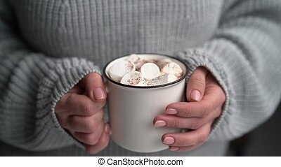 Woman holding mug with hot cacao decorated with marshmallow and chocolate
