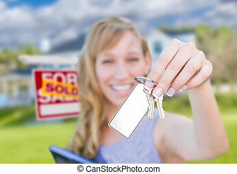 Woman Holding New House Keys with Blank Card In Front of Sold Real Estate Sign and Home.