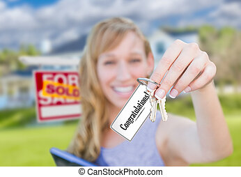 Woman Holding New House Keys with Congratulations Card In Front of Sold Real Estate Sign and Home.