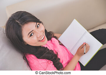 Woman holding notebook sitting on a couch, writing, looking...