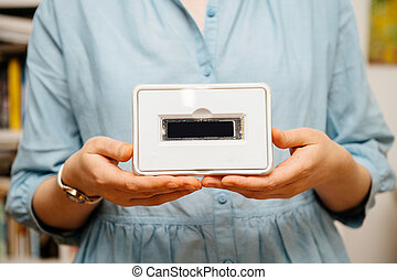 Woman holding NVME in white box - Woman hands holding new...