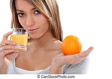 Woman holding orange and orange juice