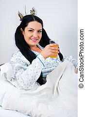 Woman holding orange juice in bed