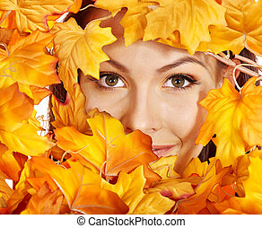 Woman holding orange leaves.