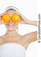 Woman holding oranges in front of eyes