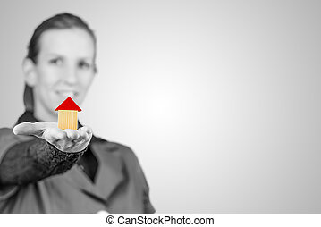 Woman holding out a model house