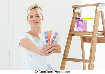 Woman holding out color swatches in new house