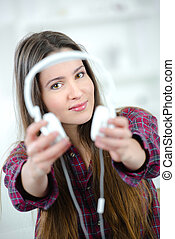 Woman holding out headphones