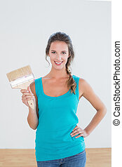 Woman holding paint brush in a new house