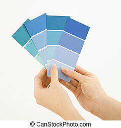 Woman holding paint swatches. - Caucasian female hands...