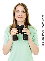 Happy woman holding pair of glasses and looking to camera standing in front