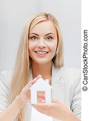 woman holding paper house