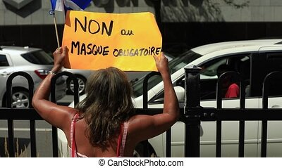 Rear view of young woman holding paper poster with non au masque obligatoire message depicting no compulsory mask while talking to man in car