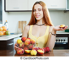 woman holding peaches at table in home