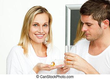 Woman holding pills and man an orange juice