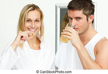 Woman holding pills and man drinking orange juice