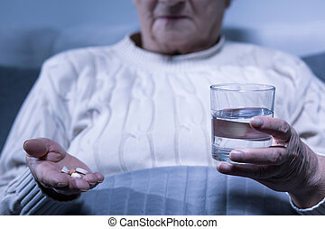 Woman holding pills and water
