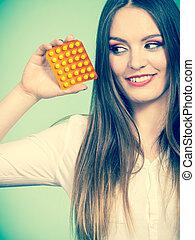 Woman holding pills blister pack vitamin c