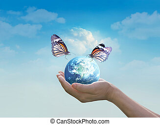 Woman holding planet earth with butterfly in hands on clean blue sky background, Elements of this image furnished by NASA