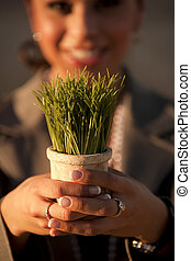 Woman holding plastic grass in pot