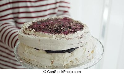 Woman holding plateu with white Meringue cake with forrest ...