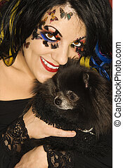 Woman holding Pomeranian dog.
