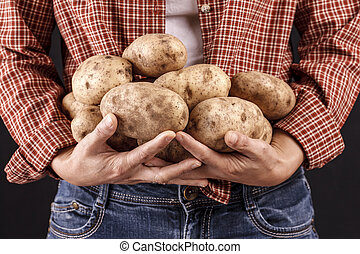 Woman holding potatoes in hands.