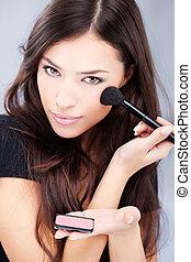 woman holding powder brush