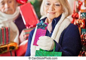Woman Holding Present In Christmas Store