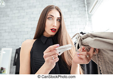 Woman holding price tag in clothing store
