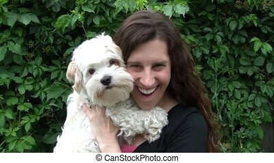 Woman Holding Puppy & Smiling