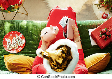 Holiday season. woman in sparkle gold sequin santa hat holding purse with money and credit cards, piggy bank and planning Christmas budget while sitting on sofa in the modern living room at Christmas.