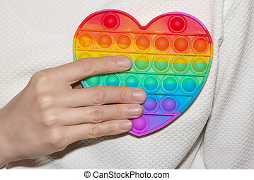 Woman holding rainbow heart in her hand close up. LGBT or GLBT concept. Pop Fidget Sensory Toy for Autism Special Needs Stress Relief in form of heart