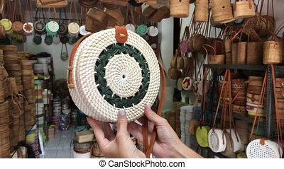 Woman holding rattan eco bags in the art shop on Bali...