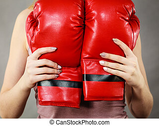 Woman holding red boxing gloves