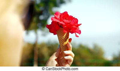 Woman holding red flowers in waffle cone - Close-up shot of...