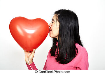 Woman holding red heart shaped balloon