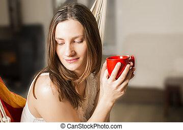 Woman holding red mug of coffee