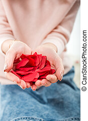 Woman holding red paper hearts