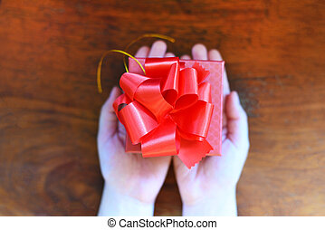 Woman holding red present box in hands for give love valentines day concept - Giving gift boxes with ribbon on wood background